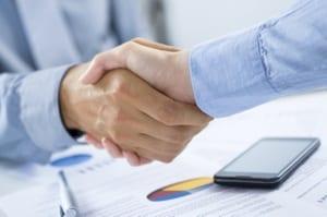 Noen som tar hverandre i hånden over en avtale