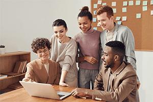 Gruppe unge som ser på en datamaskin og smiler